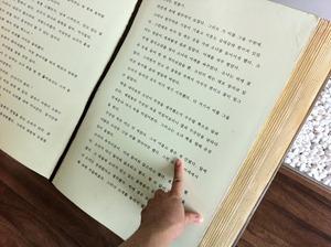 큰 글씨 책에 손가락을 가리키고 있다.