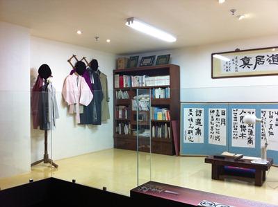 황순원의 서재, 벽에 걸린 옷과 책장, 병풍 등이 있다.