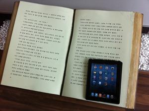 크기 비교를 위해 큰 글씨 책 위에 아이패드를 올려놓았다. 한 페이지의 크기가 아이패드의 2배가 넘는다.