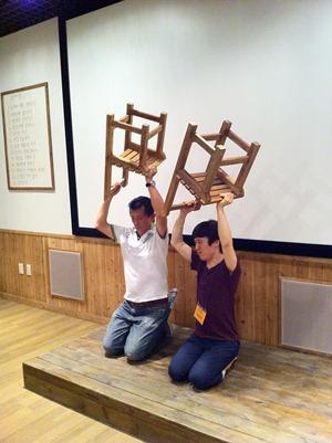 칠판앞에서 두 사람이 무릎을 꿇은채 의자를 들고 벌받는 시늉을 하고 있다.